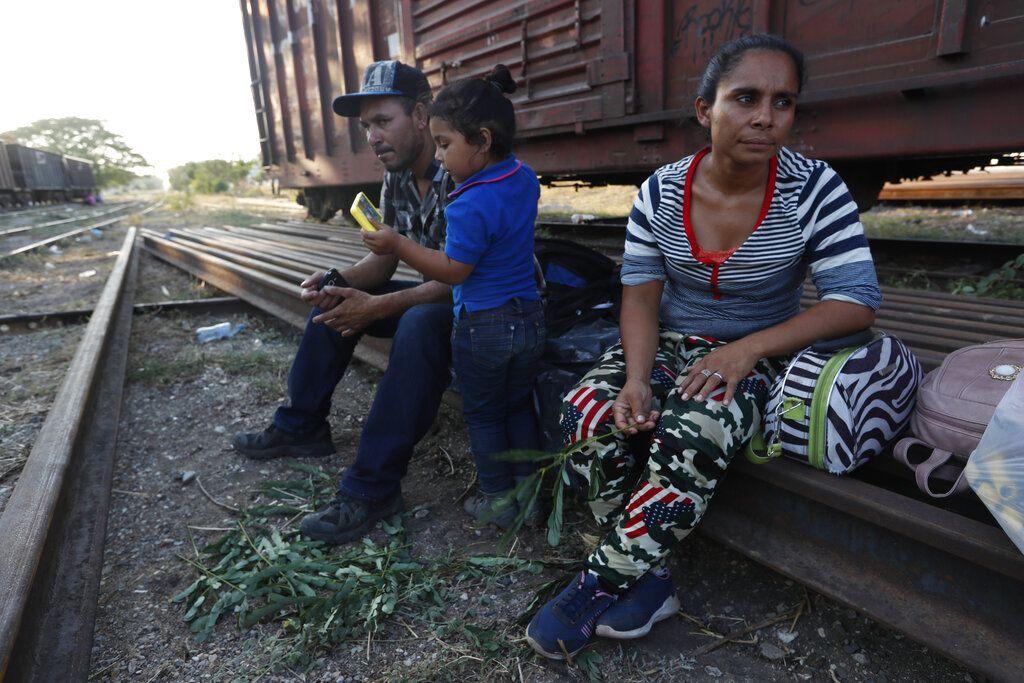 Los migrantes hondureños Sandra Montoya, su esposo José Vallecillo y su hija Brittany descansan sobre unas vías antes de que el tren de carga parta de Arriaga, estado de Chiapas, México, el miércoles 24 de abril de 2019. (AP Foto/Moisés Castillo)
