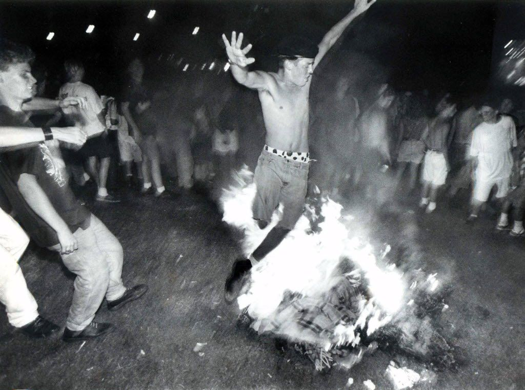 In September, 1992, a slam-dancer leaps over a bonfire at the Lollapalooza '92 festival at Starplex.