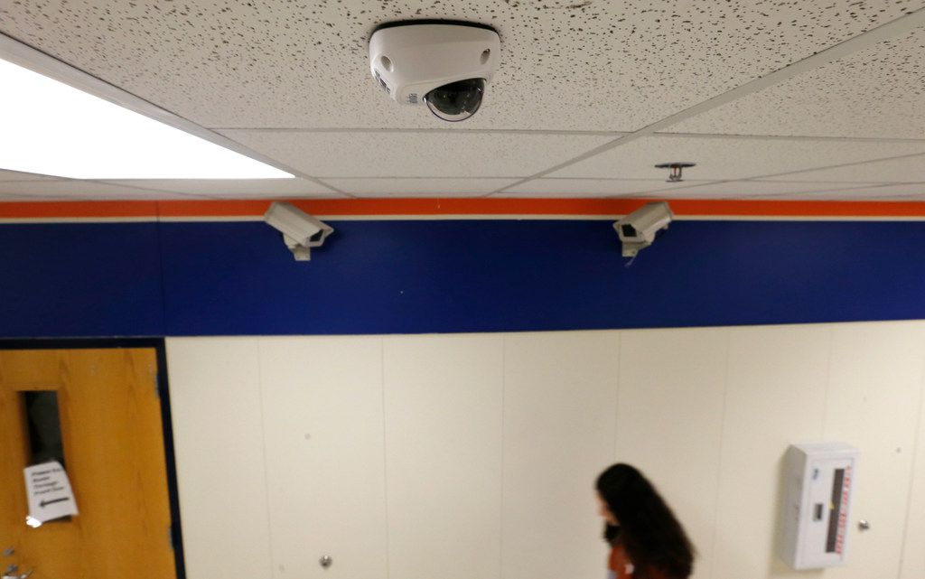 A student passes one of the new security cameras in a hallway near two of the older models at McKinney North High School.