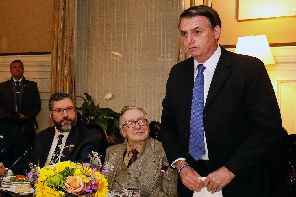 Handout picture released by the Brazilian Presidency showing Brazilian President Jair Bolsonaro (R), next to ultra-right wing guru Olavo de Carvalho (C) and Brazilian Foreign Minister Ernesto Araujo (L) during a meeting with members of his delegation and right-wing influencers at the Brazil embassy in Washington DC, United States, on March 17, 2019. (Photo by Alan SANTOS / Brazilian Presidency / AFP) / RESTRICTED TO EDITORIAL USE - MANDATORY CREDIT 'AFP PHOTO /  BRAZILIAN PRESIDENCY - ALAN SANTOS' - NO MARKETING - NO ADVERTISING CAMPAIGNS - DISTRIBUTED AS A SERVICE TO CLIENTSALAN SANTOS/AFP/Getty Images