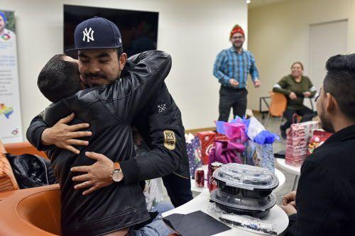 Bladi Duran, de 39 años, a la derecha, abraza a Jason Osborne, de 35, durante un intercambio de regalos en una fiesta de Navidad para LGBT Latinos en el Resource Center en Dallas, el lunes 16 de diciembre de 2018. Foto: Ben Torres / Especial para Al Día.