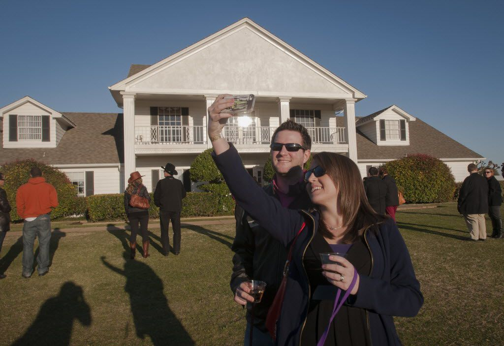 """Alyssa Shepherd, front, takes a photo of she and her husband Justin in front of Southfork Ranch in Parker  before they and other fans of the t.v. show """"Dallas""""  toast to Larry Hagman on Monday, March 11, 2013.    (Rex C. Curry/Special Contributor) 03122013xNEWS 11292013xGUIDE"""