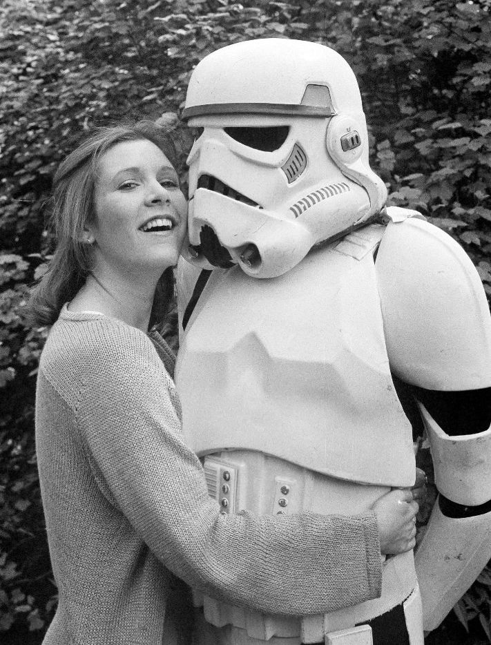 "In this May 23, 1980, file photo, actress Carrie Fisher hugs a person dressed as a stormtrooper in London while promoting the ""Star Wars"" epic ""The Empire Strikes Back."" Fisher, a daughter of Hollywood royalty who gained pop-culture fame as Princess Leia in the original ""Star Wars"" died Tuesday, Dec. 27, 2016. She was 60. (AP Photo/Dave Caulkin, File)"