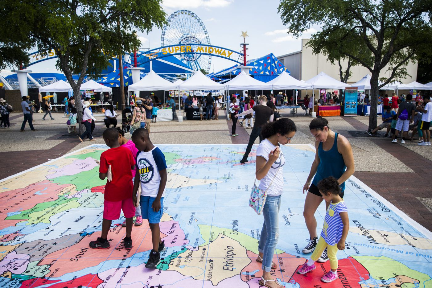 People look at a large map of Asian and Middle Eastern countries during the 27th Home Depot Asian Festival on Saturday, May 13, 2017 at Cotton Bowl Plaza in Dallas Fair Park.