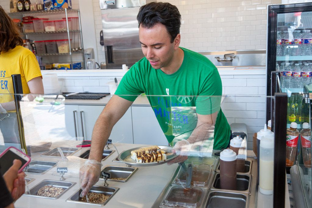 Adrian Lara, co-founder of Picole Pops, prepares a pair of popsicles at the store's Deep Ellum location.