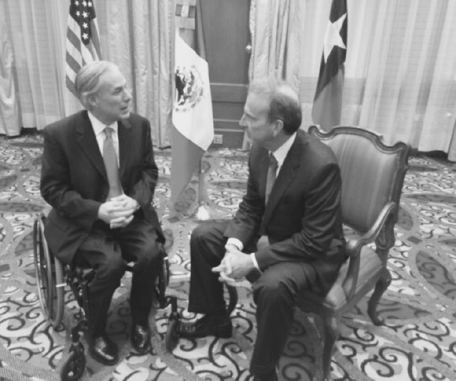 Gov. Greg Abbott confers with former U.S. Ambassador Tony Garza, a former Texas railroad commissioner, Tuesday in Mexico City.