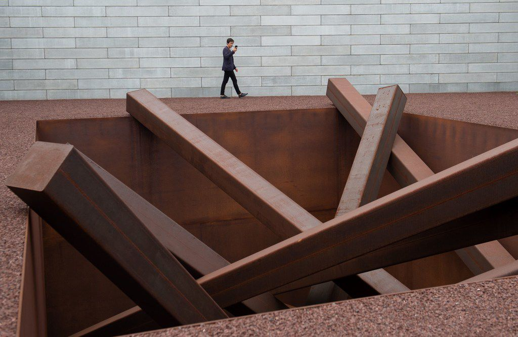 """A man tours artist Michael Heizer's """"Collapse,"""" a sculpture of 15 steel beams arranged in a 16-foot hole, as he tours the Pavilions, a new building at the Glenstone Museum, combining art, architecture and landscape."""