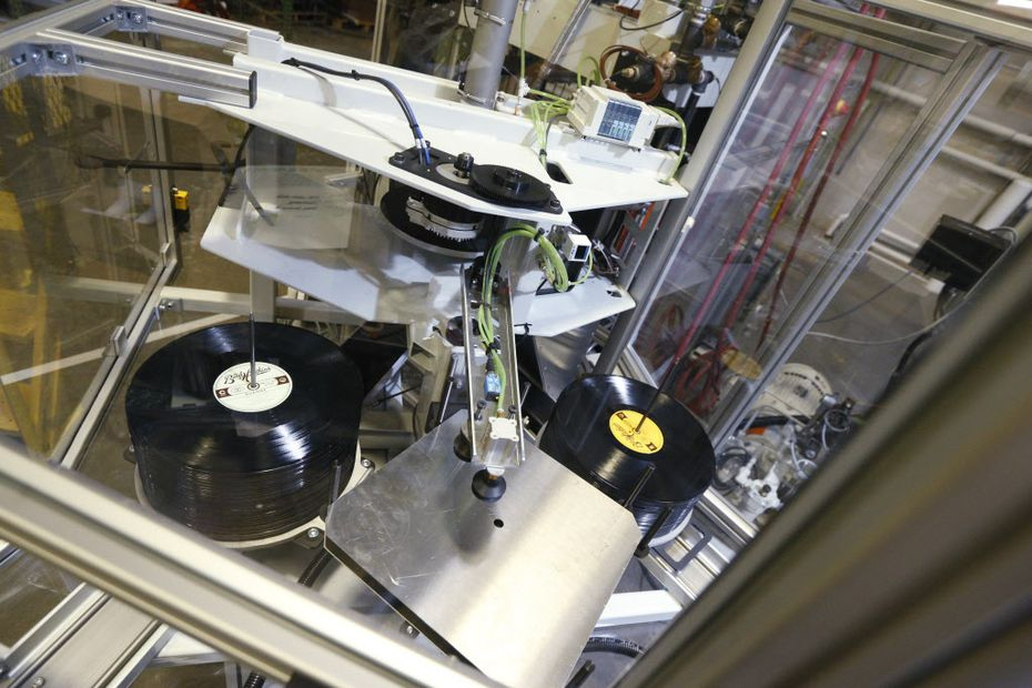 Records sit in a album press at Hand Drawn Pressing in Addison, Texas.