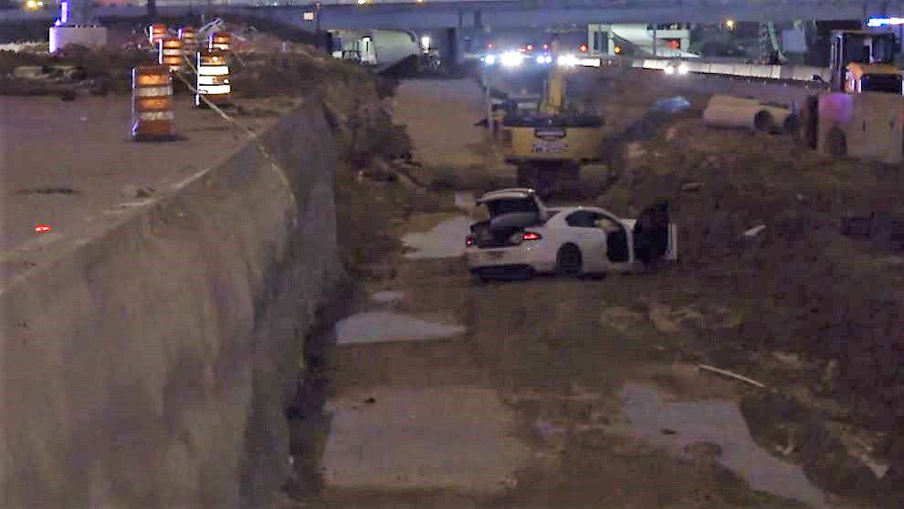 A Dodge Charger lies wrecked in a construction area along Interstate 30 in Arlington on Wednesday morning, The car wound up here after a police chase began in North Richland Hills.