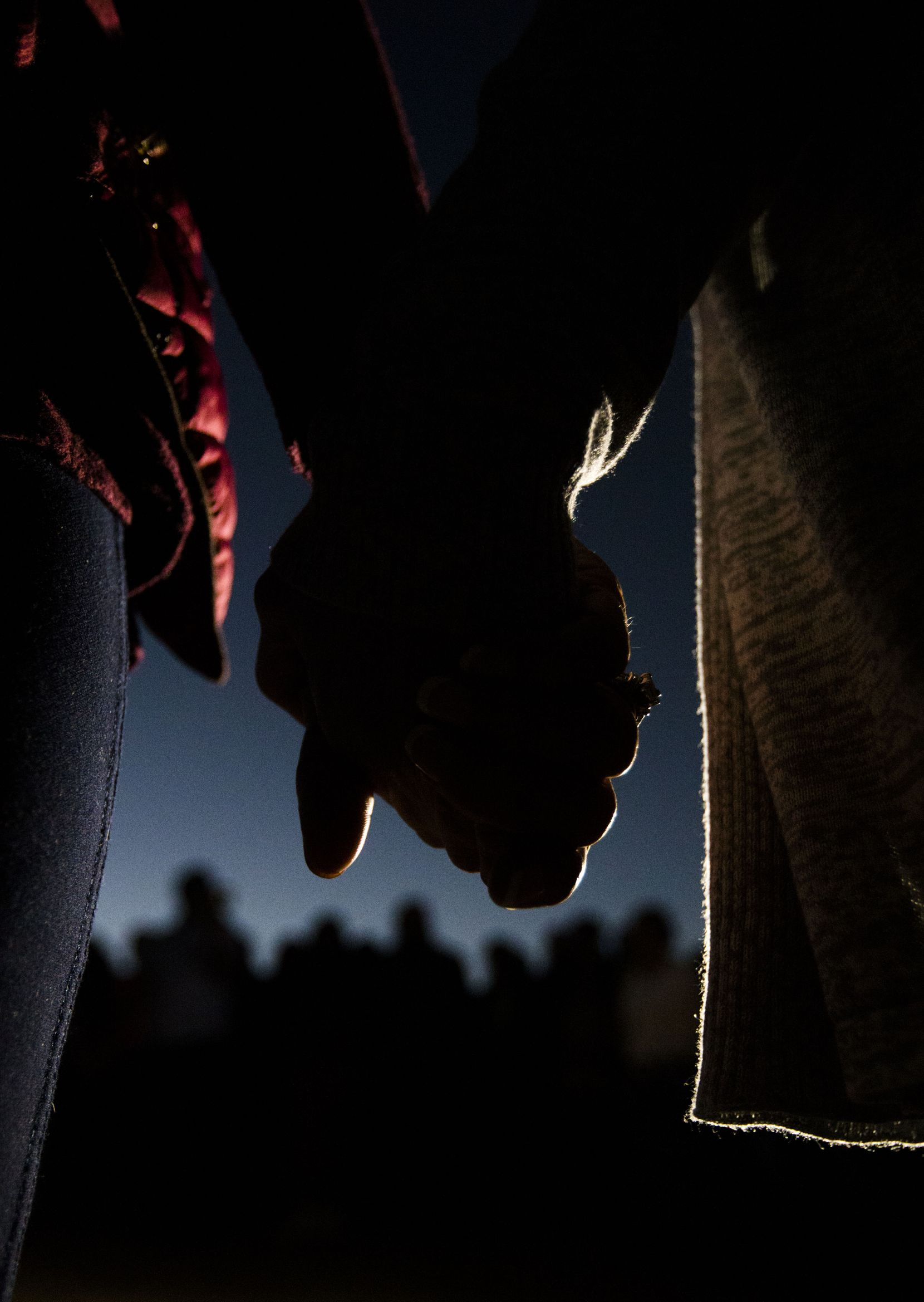 Two women held hands Sunday during a prayer vigil at a memorial for Sherin Mathews behind her home.
