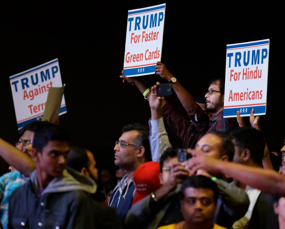 Supporters of Republican presidential candidate Donald Trump hold up signs as he speaks during a charity event hosted by the Republican Hindu Coalition, Saturday, Oct. 15, 2016, in Edison, N.J. (AP Photo/Julio Cortez)