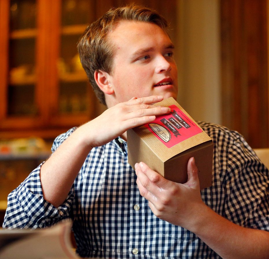 Jon Heighten has been packaging Smile Biscotti gift boxes at his parents University Park home since November.  The gifts are part of Jon's daily skills enhancement as he struggles with autism. (Tom Fox/The Dallas Morning News)