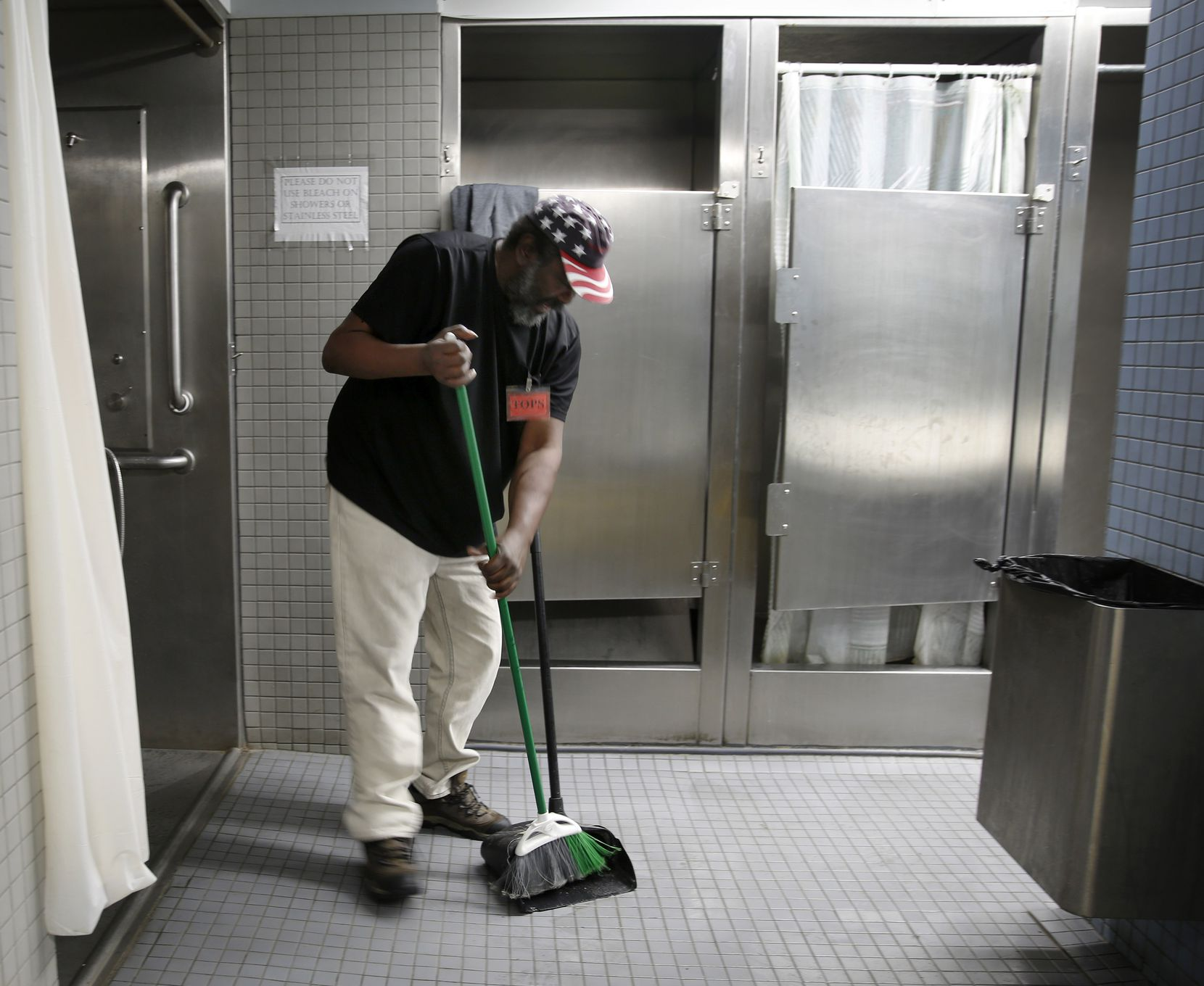 Salvation Army volunteer Kenneth Spencer cleans up the men's showers at the Carr P. Collins Social Service Center in Dallas. The taller shower doors provide more privacy to guests, including those who identify themselves as transgender.