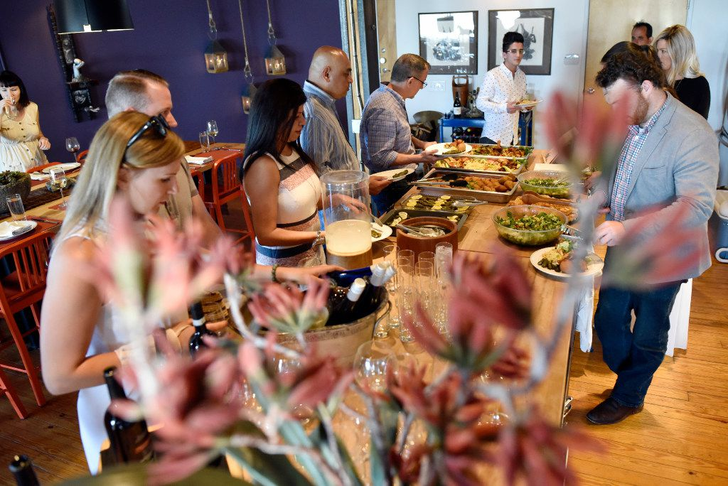 Guests serve themselves food during a fundraising dinner for the Aleid family.
