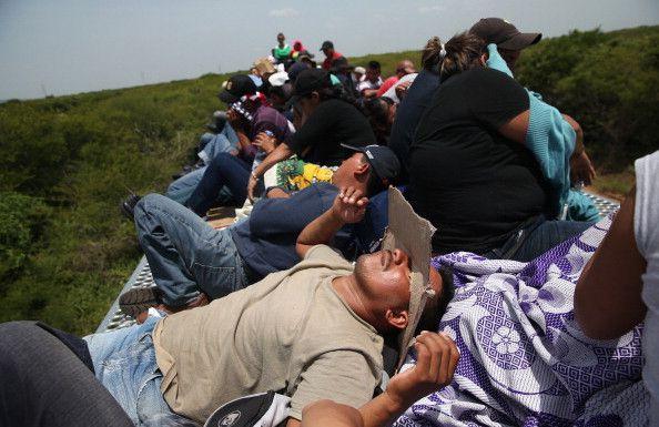"""JUCHITAN, MÉXICO. Inmigrantes centroamericanos van encima del tren de carga conocido como 'La Bestia' el 6 de agosto de 2013. """"La gente se sube a la bestia desde Chiapas o Oaxaca y es algo tradicionalmente difícil de cubrir porque montar en el tren es peligroso por naturaleza. Algunos inmigrantes son robados y asaltados por pandillas que controlan las copas de los trenes, mientras que otros se duermen y caen, pierden miembros o perecen bajo las ruedas de los trenes. Yo solo estuve allí 3 horas. Estaba en un refugio hablando con los muchachos de cómo subirme al tren. Me advirtieron que no tendría tiempo para practicar sino que saltara apenas el tren hiciera la curva. En movimiento. El camino es plano y se puede subir, pero aún así la gente se sorprendió cuando lo hice"""". Foto: John Moore / Getty Images"""