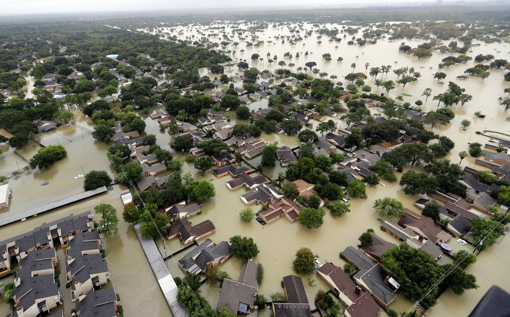 In this Aug. 29, 2017, water from Addicks Reservoir flows into neighborhoods from floodwaters brought on by Tropical Storm Harvey in Houston. This week, the Texas Legislature sent a bill to Gov. Greg Abbott that would allow Texans to openly carry handguns for a full week after a natural disaster.