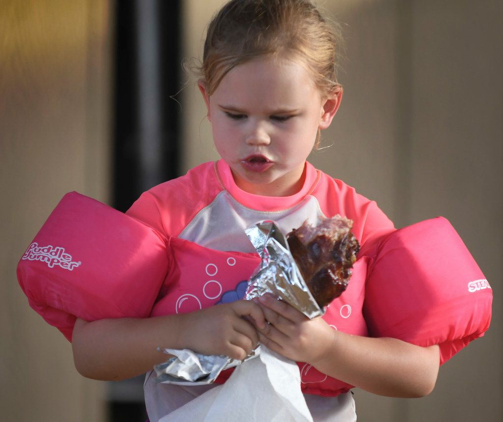 Five-year-old Amelia Whiteman of Dallas chews on a turkey leg during Rockin'€™ the River at Panther Island in Fort Worth.