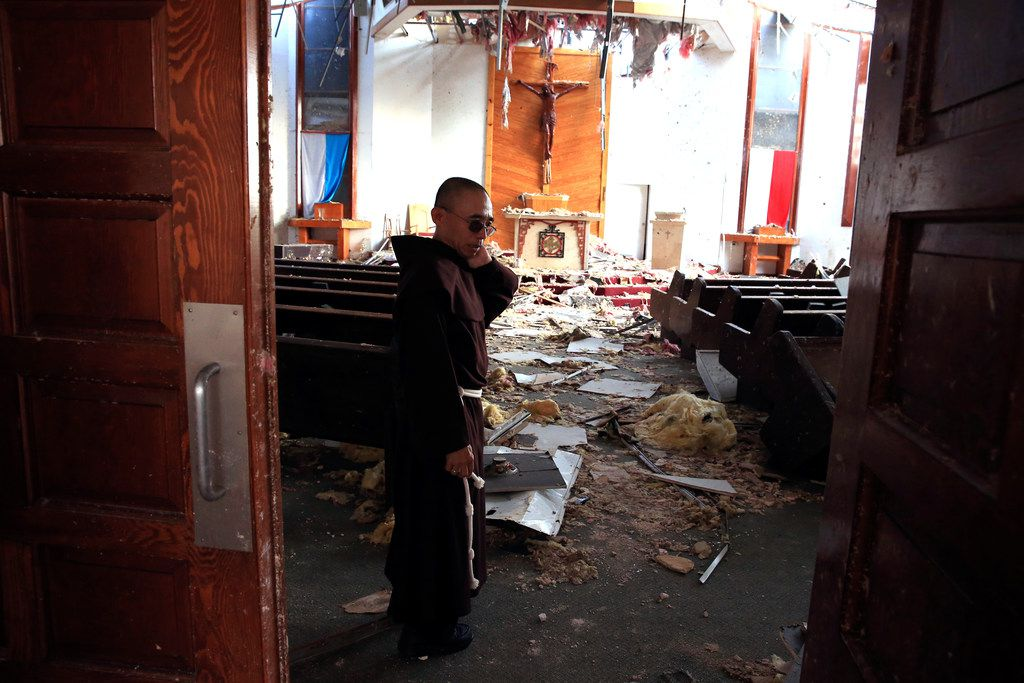 Fr. John Tran Nguyen looks around the heavily damaged St. Peter Catholic Church in Rockport on Sept. 14. The church was damaged during Hurricane Harvey.