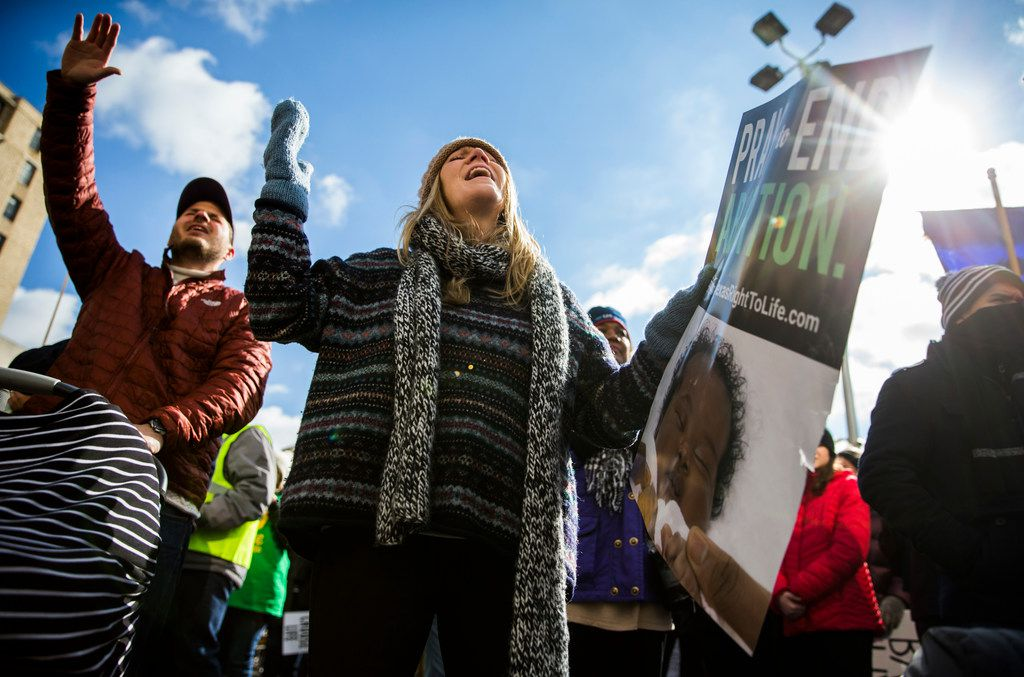 Mallory Goerk, center, and David Goerk, left, sing and hold signs as they and demonstrators rally after marching from Cathedral Shrine of the Virgin of Guadalupe to Earle Cabell Federal Courthouse during the North Texas March for Life on Saturday, January 19, 2019 in downtown Dallas.