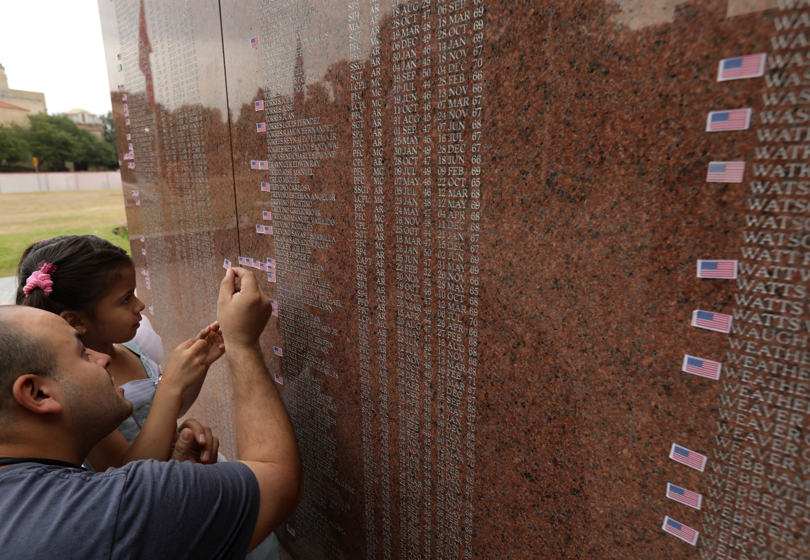 Omar Bravo and 6-year-old Caroline Bravo place a memorial flag sticker on one of the names engraved on the Texas Vietnam Veterans Memorial at Fair Park on Monday. They were two of the hundreds who have visited the monument during this year's fair.