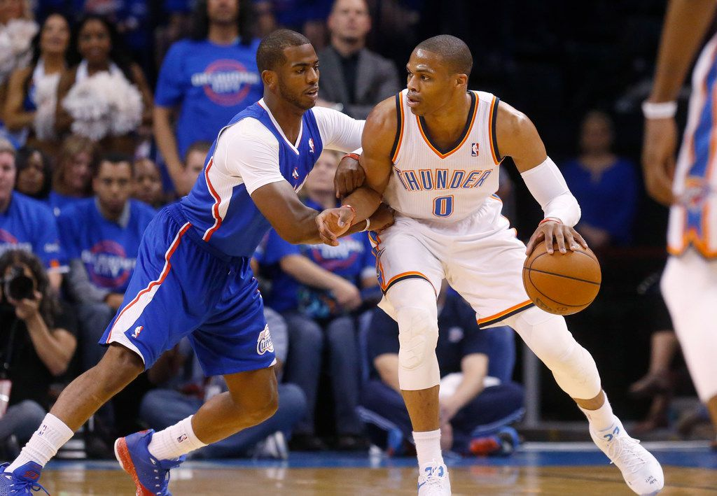 FILE - In this Monday, May 5, 2014 file photo, Oklahoma City Thunder guard Russell Westbrook (0) drives against Los Angeles Clippers guard Chris Paul (3) in the first quarter of Game 1 of the Western Conference semifinal NBA basketball playoff series in Oklahoma City.  A person with knowledge of the situation says the Oklahoma City Thunder have traded Russell Westbrook to the Houston Rockets for Chris Paul, a shake up of top point guards and a move that reunites Westbrook with James Harden, Thursday, July 11, 2019. (AP Photo/Sue Ogrocki, File)