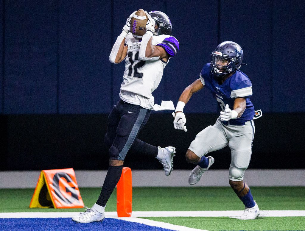 Frisco Independence receiver Zhighlil McMillan (12) catches a pass ahead of Frisco Lone Star defensive back Tyron Hall (8) before stepping across the goal line for a touchdown during the fourth quarter of a District 5-5A Division I high school football game between Frisco Independence and Frisco Lone Star on Thursday, October 10, 2019 at the Ford Center at The Star in Frisco. (Ashley Landis/The Dallas Morning News)