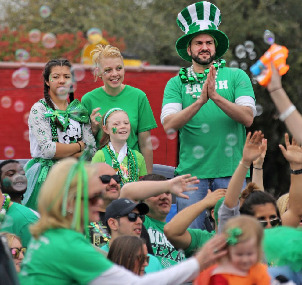 Parade spectators enjoy the bubbles floating through the air from a float during the Dallas St. Patrick's Parade & Festival along Greenville Avenue in Dallas on Saturday.