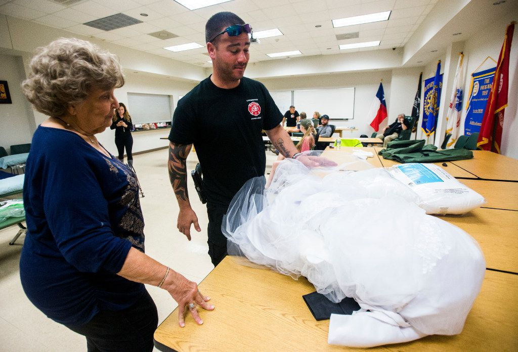 Joyce Brown, left, office manager of the Lumberton Central Fire Station, talks to Firefighter Kyle Parry, who retrieved the wedding dress of his fiancé, Stephanie Hoekstra, not pictured, of Chatham-Kent, Ontario, Canada, from his home, which is flooded as a result of Tropical Storm Harvey on Thursday, August 31, 2017 in Lumberton, Texas. Parry and Hoekstra are supposed to be married on September 10 in Galveston. Parry's home is destroyed, but he was able to retrieve the dress. (Ashley Landis/The Dallas Morning News)