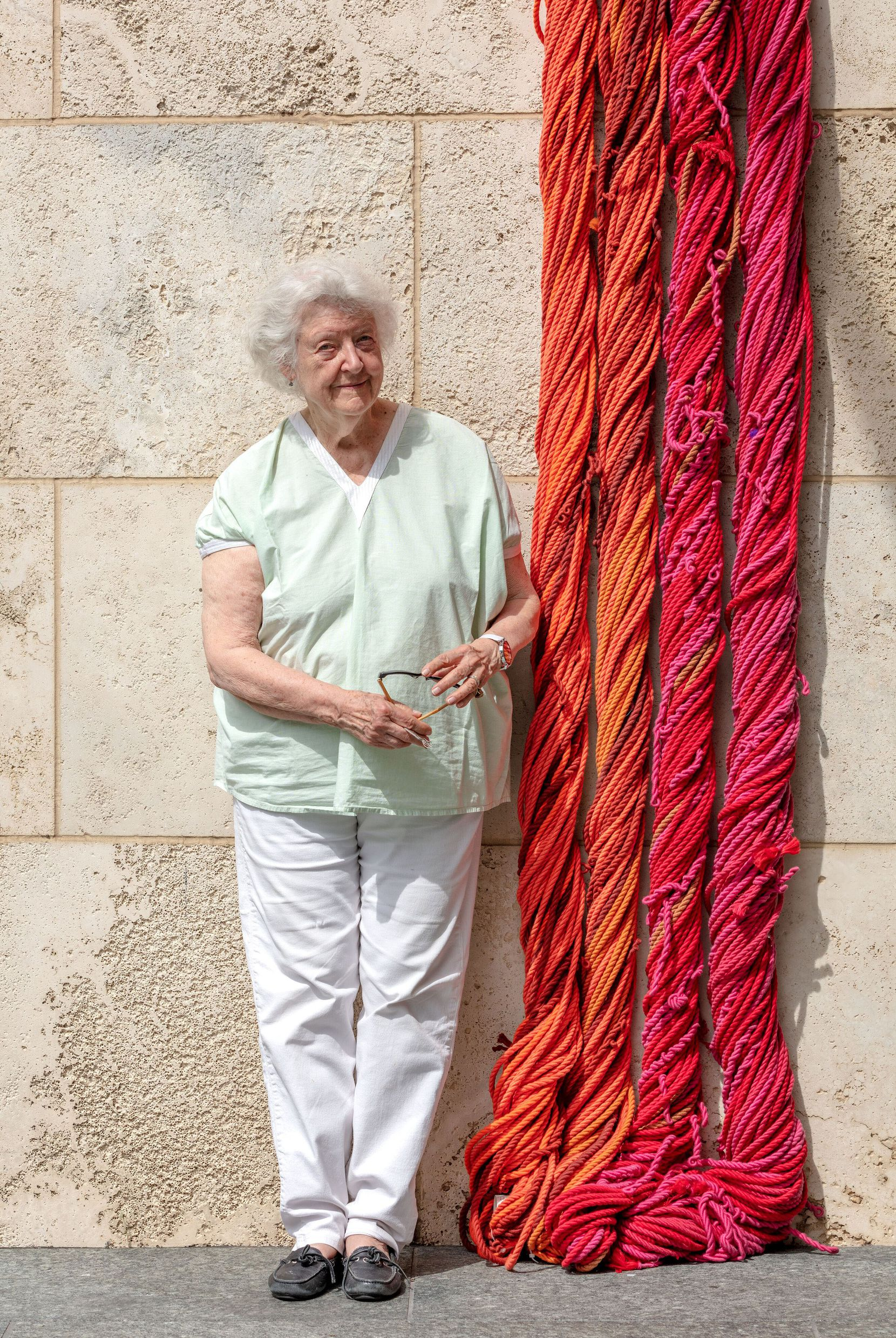"""Artist Sheila Hicks poses with a part of her """"Sheila Hicks: Seize, Weave Space"""" 2019 installation, on view through Aug. 18 at the Nasher Sculpture Center in Dallas."""