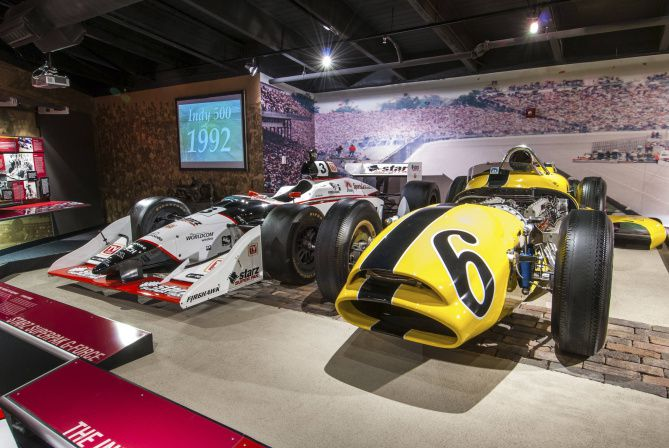 Newer and older Indy cars sit on display in the Unser Racing Museum in Albuquerque.  The white #3 car was raced by Al Unser Junior in the 2001 Indy 500 and the yellow #6 was a Novi driven by Bobby Unser in the 1963 race.