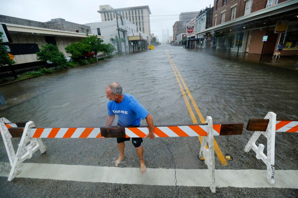 John Alvarez, owner of Galveston Coffee Roasters in the historic Strand District borrowed traffic barriers from a nearby construction site to close off traffic.  The wake from trucks was causing water to flood his business. The city of Galveston, Texas was flooded from punishing overnight rains from Tropical Storm Harvey which passed by the island, Tuesday, August 29, 2017. (Tom Fox/The Dallas Morning News)
