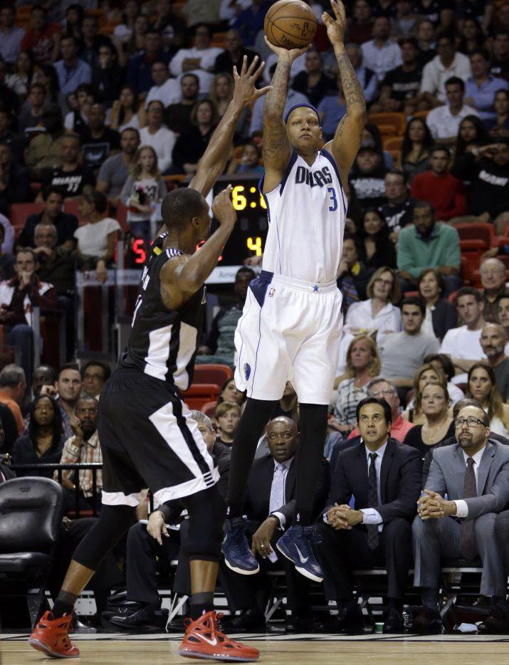 Dallas Mavericks forward Charlie Villanueva (3) prepares to shoot a three-pointer against Miami Heat center Chris Bosh (1) in the second half of an NBA basketball  game in Miami, Friday, Jan. 30, 2015. The Mavericks won 93-72. (AP Photo/Alan Diaz)