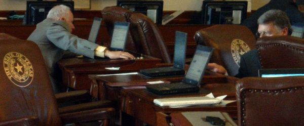 In a frame grab from video, Texas State Rep. Allan Ritter, District 21 (R-Nederland), (left) is captured using his right hand to cast votes his own name, while simultaneously using his left hand to press the button to vote on behalf of the fellow Republican House member to his left, who was not at their desk at the time, during Texas House proceedings on Wednesday. At right, Rep. Chuck Hopson, District 11 (R-Jacksonville), is also captured turning around in his chair to vote on behalf of the absent member sitting at the desk behind him.