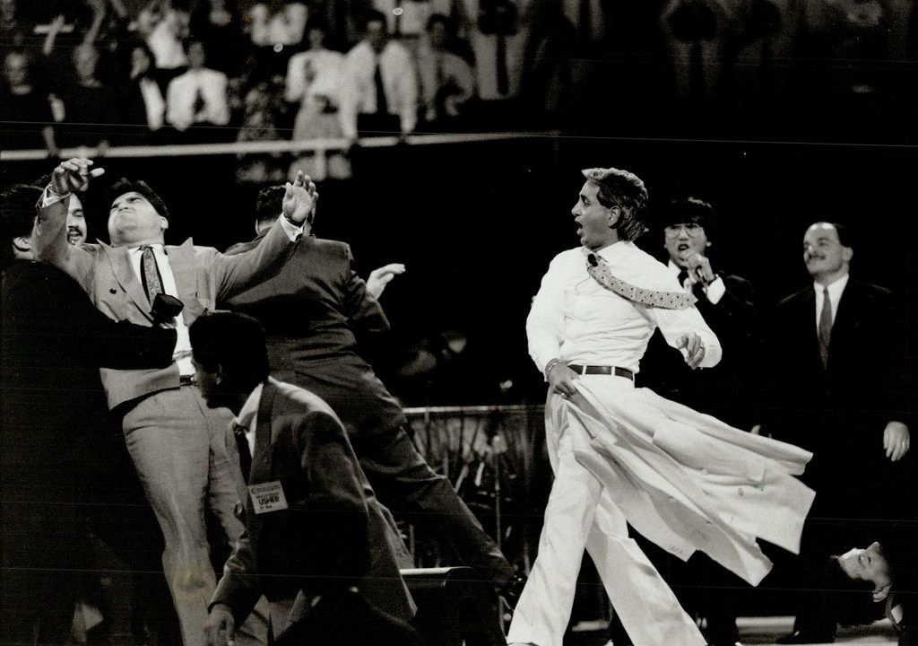CANADA - SEPTEMBER 28, 1992:  Benny Hinn: At left; and above; during Maple Leaf Gardens performance where he waved his coat about; proclaiming people cured of their ailments.