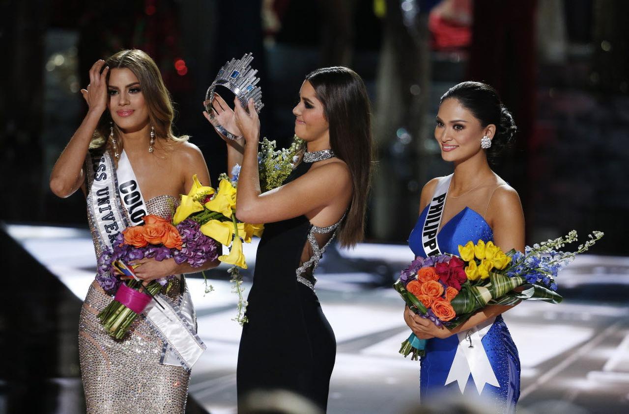 La anterior Miss Universe Paulina Vega le quita la corona a Ariadna Gutiérrez de Colombia, luego de rectificar un error del presentador del título de Miss Universe, el domingo en Las Vegas.(AP)