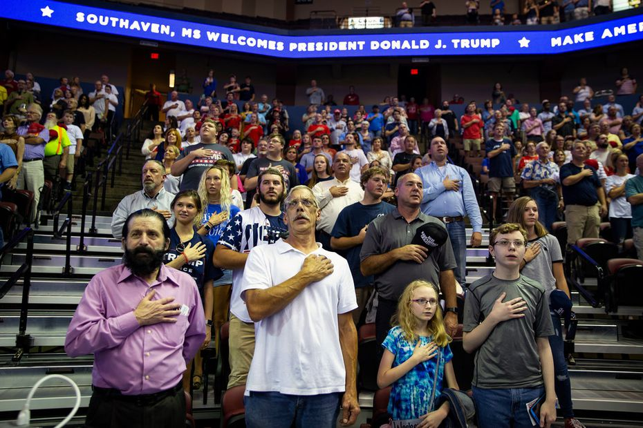 People stand for the national anthem before President Donald Trump speaks at a rally in Southaven, Miss., on Oct. 2, 2018.