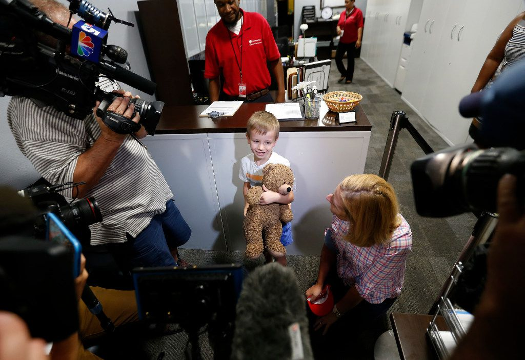 Luke Swofford, 4, and his mother Nikki Swofford talk with the media inside the Lost and Found office after the family picks up his teddy bear.