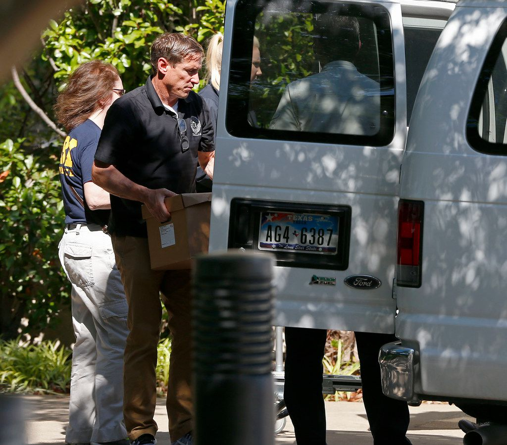 A federal agent loads boxes into a van at Medoc Health Services in Dallas on Wednesday.