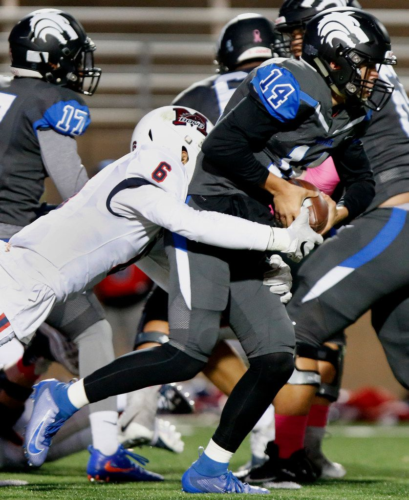 Plano West High School quarterback Andrew Picco (14) is tackled by \mbduring the first half as Plano West High School hosted McKinney Boyd High School at Clark Stadium in Plano on Friday night, October 11, 2019. (Stewart F. House/Special Contributor)