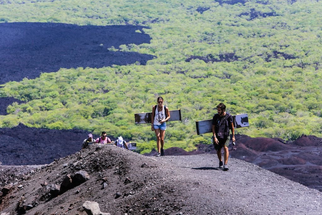 Tourists climb the Cerro Negro volcano with their boards. The hike up to the peak is steep and can take anywhere from one to three hours.