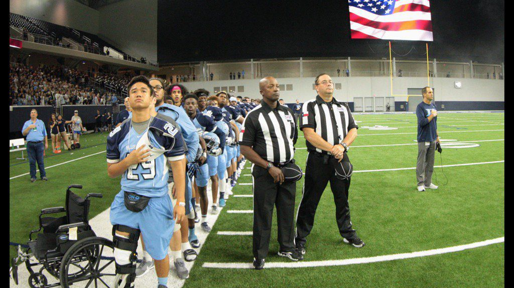 Hurst L.D. Bell junior Vita Tonga stands with his teammates for the National Anthem a day after ACL surgery on Saturday Sept. 10, 2016 (photo courtesy of Charlie Tonga).