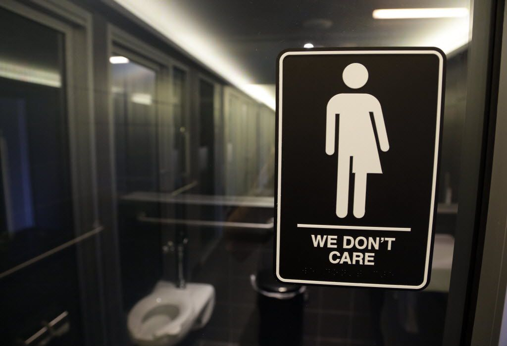 FILE - This Thursday, May 12, 2016, file photo, shows signage outside a restroom at 21c Museum Hotel in Durham, N.C. North Carolina is in a legal battle over a state law that requires transgender people to use the public restroom matching the sex on their birth certificate. Some small business owners already working to make their companies more welcoming to LGBT employees say the massacre at a gay dance club in Orlando, Fla., gives them an impetus to make more changes. In this photo, the Americans with Disabilities Act-compliant bathroom sign was designed by artist Peregrine Honig. (AP Photo/Gerry Broome, File)