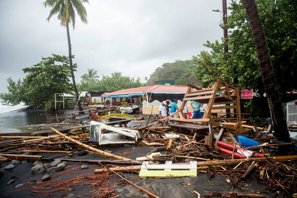 People stand next to debris at a restaurant in Le Carbet, on the French Caribbean island of Martinique, after it was hit by Hurricane Maria, on September 19, 2017. Hurricane Maria smashed into the eastern Caribbean island of Dominica on September 19, with its prime minister describing devastating damage as winds and rain from the storm also hit territories still reeling from Irma. Martinique, a French island south of Dominica, suffered power outages but avoided major damage. / AFP PHOTO / Lionel CHAMOISEAULIONEL CHAMOISEAU/AFP/Getty Images