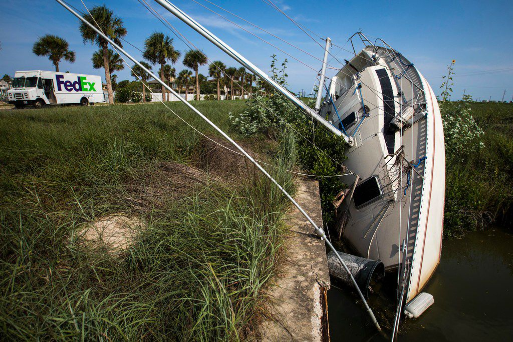 A sailboat sits stranded in a drainage canal along Mustang Boulevard in Port Aransas almost a year after Hurricane Harvey dumped it there as the storm slammed the Texas Gulf Coast.