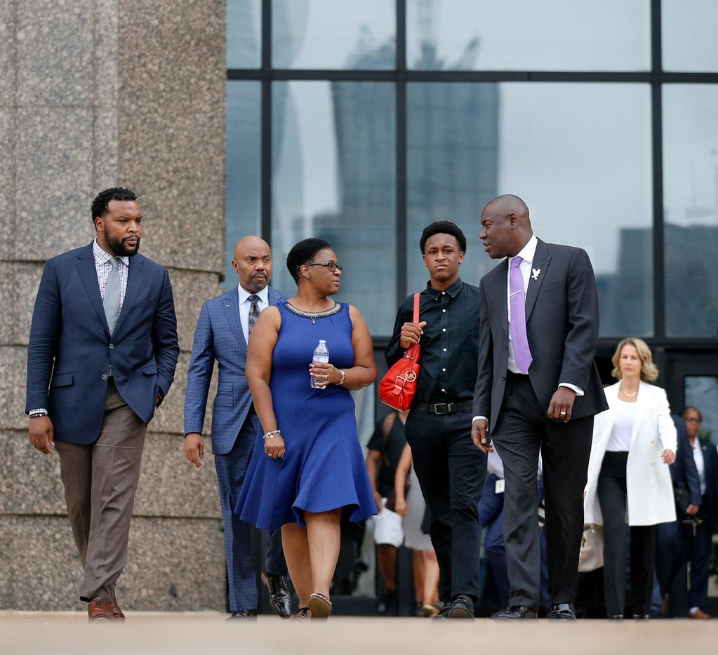 Flanked by her attorneys Lee Merritt (left) and Benjamin Crump (right), mother of shooting victim Botham Jean, Allison Jean and her other son Brandt Jean walk to a family press conference outside the Frank Crowley Courts Building.