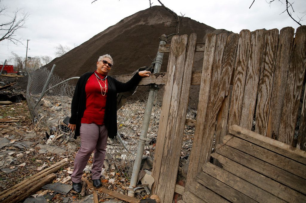 Homeowner Marsha Jackson looks over her damaged fence at the large mounds of shredded roofing shingles.  She is tired of the late night and early morning grinding of shingles that takes place outside her bedroom window in southeast Dallas,