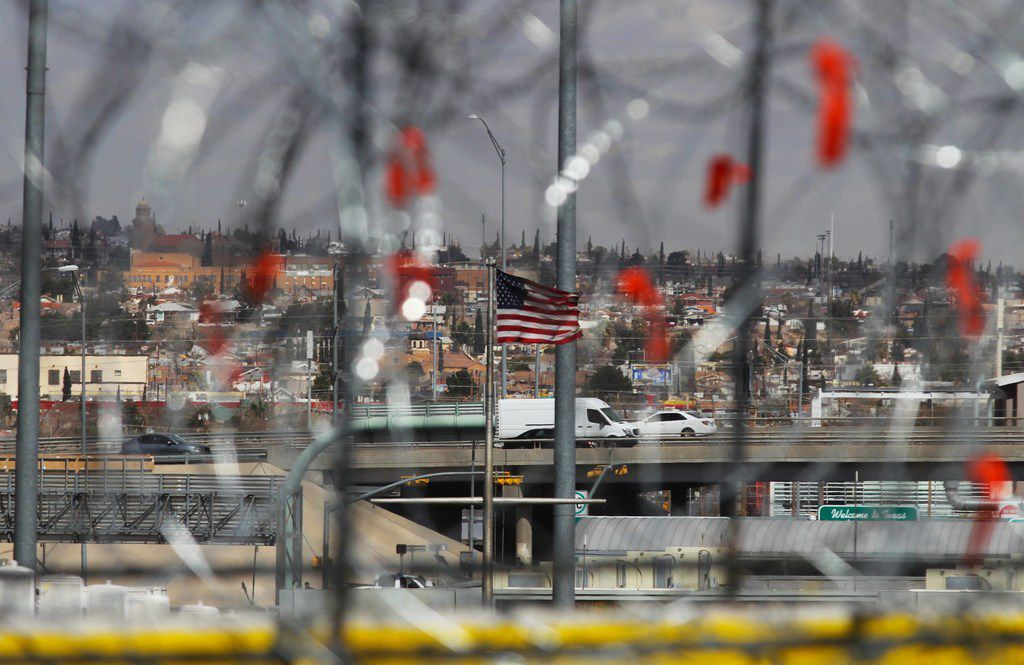 A U.S. flag flutters in the wind as barbed-wire barriers are being installed at the Zaragoza International Bridge on the U.S.-Mexico border on February 22, 2019.