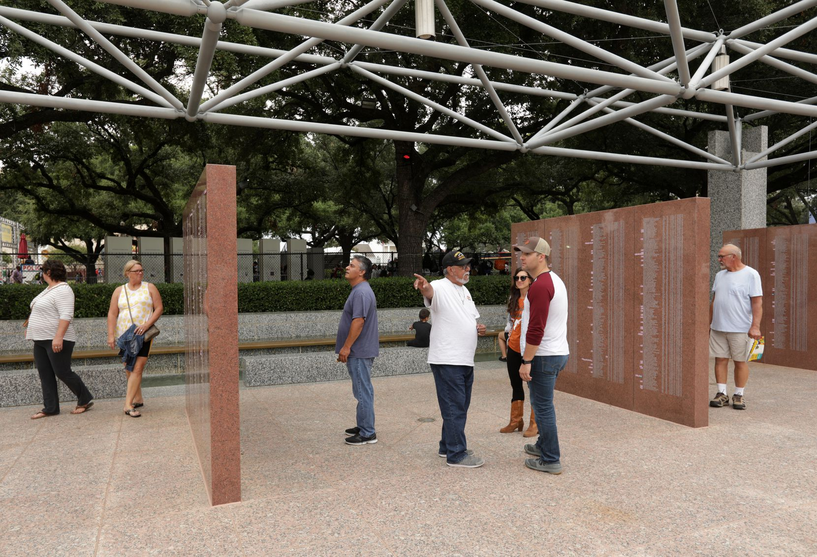 Vietnam veteran Tommy Acosta, center, talks to first-time fairgoers Ashley Servi and Chad Kozar at the memorial, which is informally called the Texas Wall. The 30-year-old Kozar says he feels a special kinship to all Vietnam veterans because, as a Marine, he served in Afghanistan.