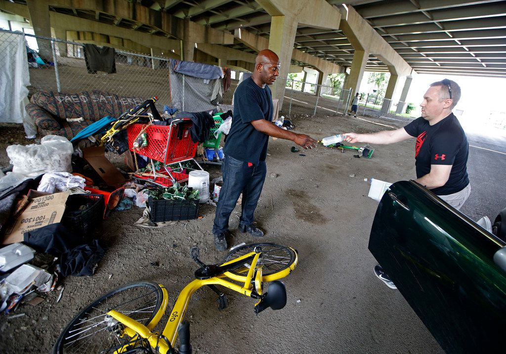 Terrance Bennett (left) receives a water from James Whisenant, who gives food to the homeless at Hill St. under Interstate 30 in Dallas on May 22, 2018. Whisenant is not affiliated with any religious or charity organization.