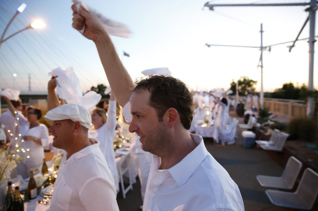 Ben Millice waves his napkin to signal dinner time during the inaugural Diner en Blanc Dallas on the Continental Avenue Bridge in Dallas on Sept. 17, 2015. Exactly 1,678 people attended the event, which requires dinner guests to dress all in white and bring their own tables, chairs and centerpieces. As per tradition, the location was kept private leading up to the event.
